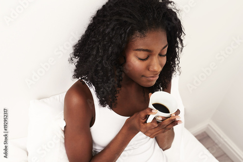 Morning coffee for beautiful young woman in bed