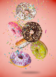 Tasty doughnuts in motion falling on pastel red background. - 192956998
