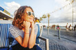 Quadro young beautiful woman girl in a striped T-shirt sitting in a street cafe smiling, seaside town, vacation and travel