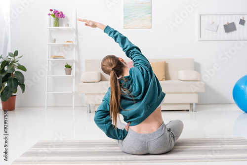 rear view of girl sitting in lotus position and stretching on yoga mat at home