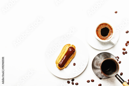 Sticker Morning coffee with eclair cake, white background, top view