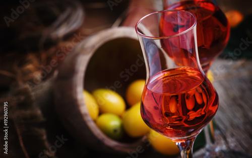 Traditional greek kumquat liqueur in shot glass, vintagen background, rustic style, selective focus