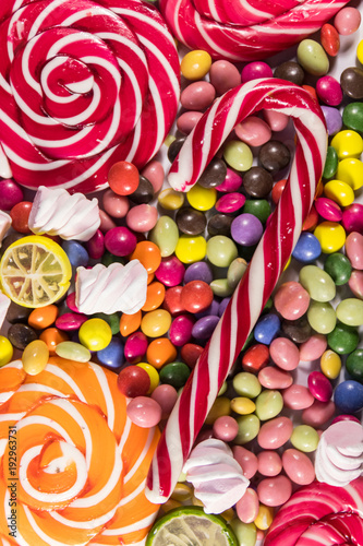 Fototapeta Background of colorful chocolate candies, lollipops, candy cane and marshmallows