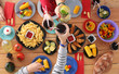 Top view of group of people having dinner together while sitting at wooden table. Food on the table. People eat fast food. - 192965753