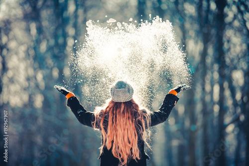 Młodej dziewczyny miotania śnieg w powietrzu przy pogodnym zima dniem, tylny widok