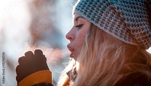 Foto Murales Woman breathing on her hands to keep them warm in cold winter day