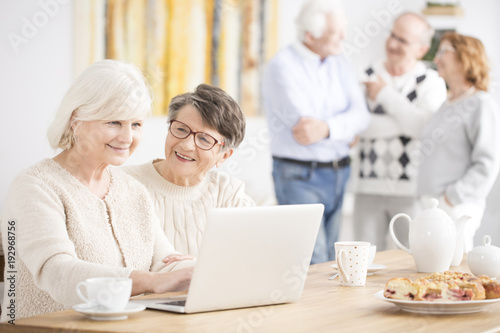 Happy elderly women using laptop