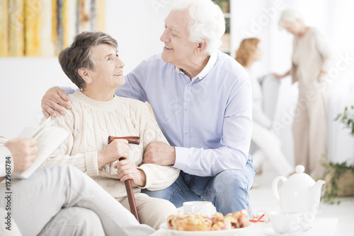 Happy elderly man hugging wife