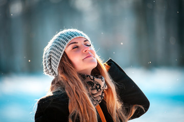 Young woman walking in winter park at sunny day