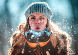 Fototapety Winter woman blowing snow outdoor at sunny day, flying snowflakes