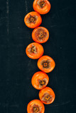 top view of row of persimmons on black - 192975383