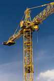 Construction crane tower on background of  blue sky. Crane and building working progress on construction site. Yellow lifting faucet.  Space for text . Vertical photo