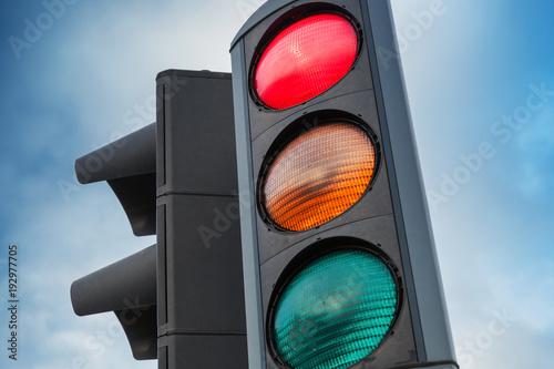Urban traffic lights over blue cloudy sky