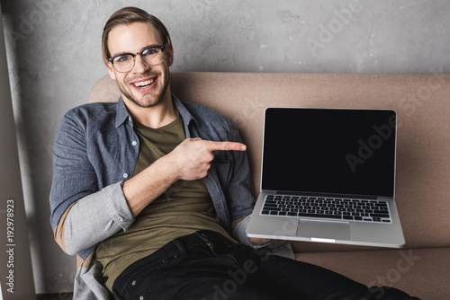 Fototapeta young smiling man sitting on couch and pointing at laptop screen