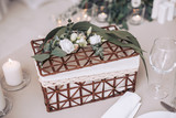 Wicker wooden basket decorated with flowers. Decorative element for the wedding ceremony - 192979784