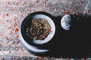 Mixed colorful grains of pepper in a mortar