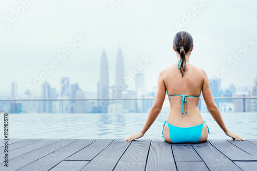 Fotobehang Kuala Lumpur Vacation in Kuala-Lumpur. Pretty young woman sittiing near roof top swimming pool with beautiful city view.