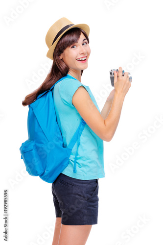 Travel concept. Studio portrait of pretty young woman with backpack holding camera. Isolated on white.