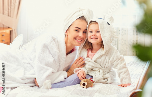 Mother and daughter in bathrobes and towels on the bed in the room. Mothers day.