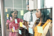 Three Indian employees sticking reminders on glass wall with business tasks and deadlines in the office - 192987328