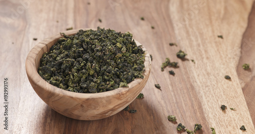 dried green tea leaves falling into wood bowl on table