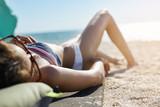 beautiful woman sunbathing on the beach. woman enjoys summer vacation - 192993962
