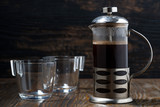 freshly brewed coffee in the french press on wooden table