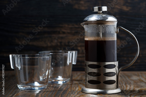 Sticker freshly brewed coffee in the french press on wooden table