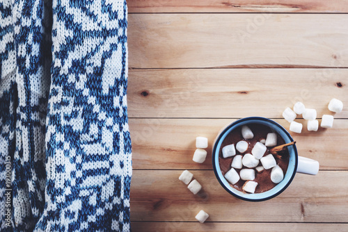 a cup of hot chocolate with marshmallow on wooden table background.