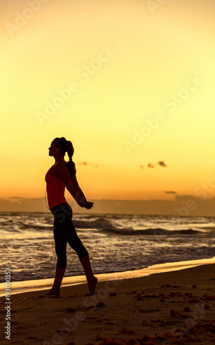 Staande foto Zwavel geel Silhouette of healthy woman in sportswear on seacoast stretching