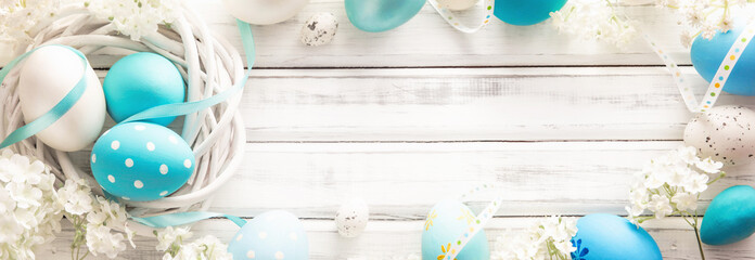 Easter Decoration with Eggs and Flowers on White Wooden Background © Maksim Pasko