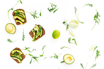 Have a bite with healthy snacks. Avocado toast on white background top view
