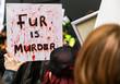 Protester in crowd with 'Fur is murder' sign