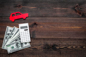 Car credit concept. Money and calculator near car silhouette on dark wooden background top view copy space