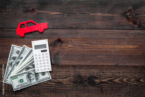 Fototapeta Car credit concept. Money and calculator near car silhouette on dark wooden background top view copy space