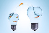 Gold fish jumping out from the smaller light bulb shaped aquarium to a bigger one - 193010723