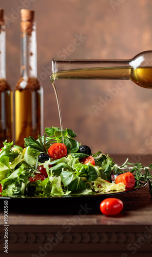 Green salad with olive oil pouring from a small bottle. - 193015568