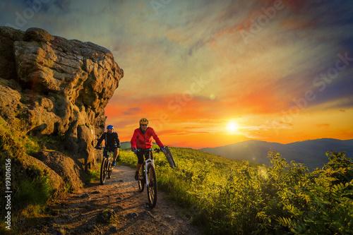 Kolarstwo górskie kobiety i mężczyzna jazda na rowerach przy zmierzchu gór lasu krajobrazem. Para rowerowa MTB enduro przepływu ślad szlaku. Aktywność na świeżym powietrzu.