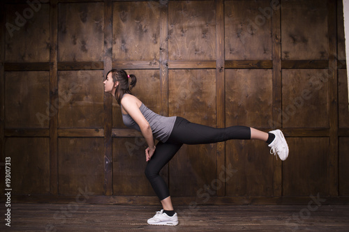 Woman in training uniform and white sneakers diong sport in gym.