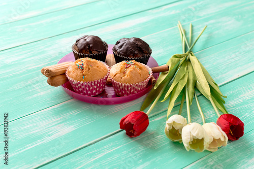 chocolate cupcakes with cookies and tulips on green wooden background © feelmax
