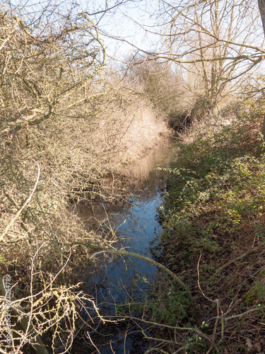 Aluminium Lente running stream through countryside below trees to side bare spring