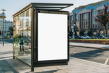 Vertical blank white billboard at bus stop on city street. In the background buildings and road. Mock up. Poster on street next to roadway. Sunny summer day.