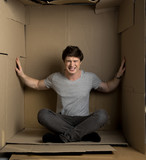 Need more space concept. Full length portrait of young depressed man is sitting in cardboard box. He is pressuring on walls while trying to extend them - 193040316
