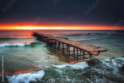 Stary łamający most w morzu, długi ujawnienie. HDR