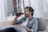 Self distraction. Unshaved uncombed man sitting on a sofa and looking awful while suffering from alcohol addiction and drinking from a bottle in his hand