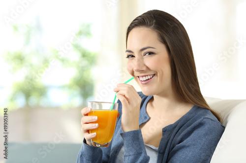 Pretty woman drinking orange juice looking at camera