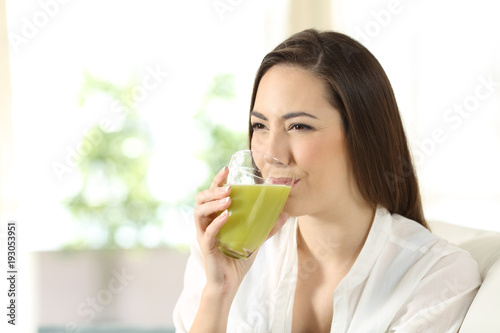 Foto op Canvas Sap Woman drinking a green vegetable juice at home