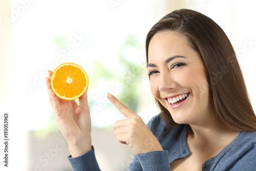 Woman showing half orange slice