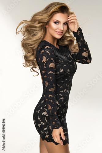 Sensual beautiful blonde woman posing in black dress. Girl with long curly hair.