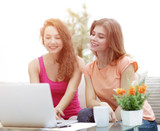 two student girls looking at laptop screen while sitting on the  - 193063991